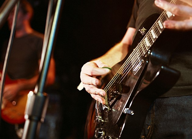 Closeup of person playing guitar
