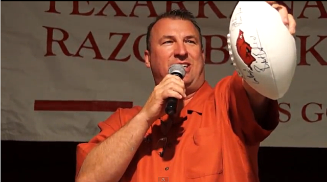 Coach Bielema auctioning a football - Mimi Campbell McDaniel/Townsquare Media