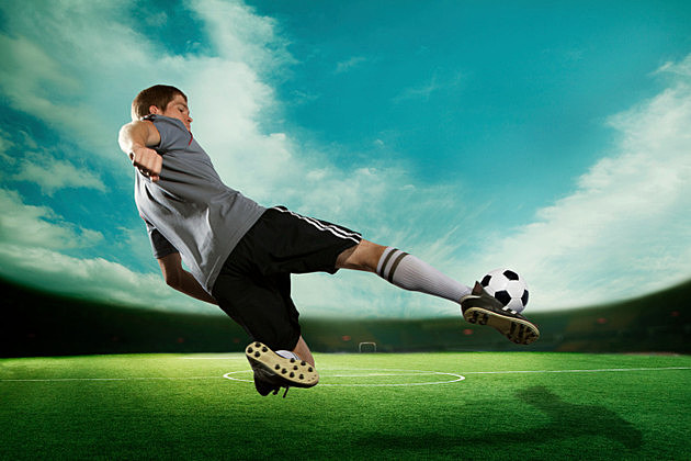 Soccer player kicking the ball in mid air