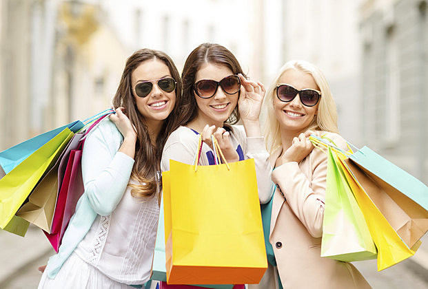 three smiling girls with shopping bags in ctiy