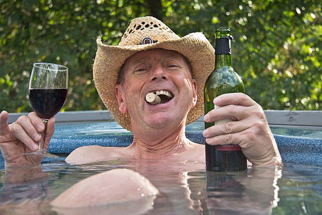 Man wearing cowboy hat sitting in hot tub with wine.