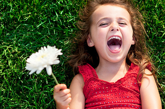Happy little girl laying on the grass holding a flower